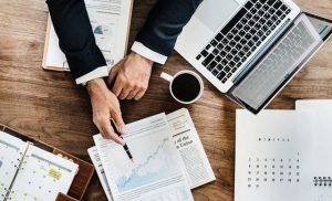 Business Process Outsourcing Agenda Tisch Kaffee Laptop Hand mit Stift